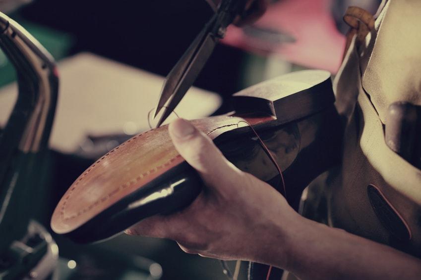artisan cordonnier effectue un ressemellage